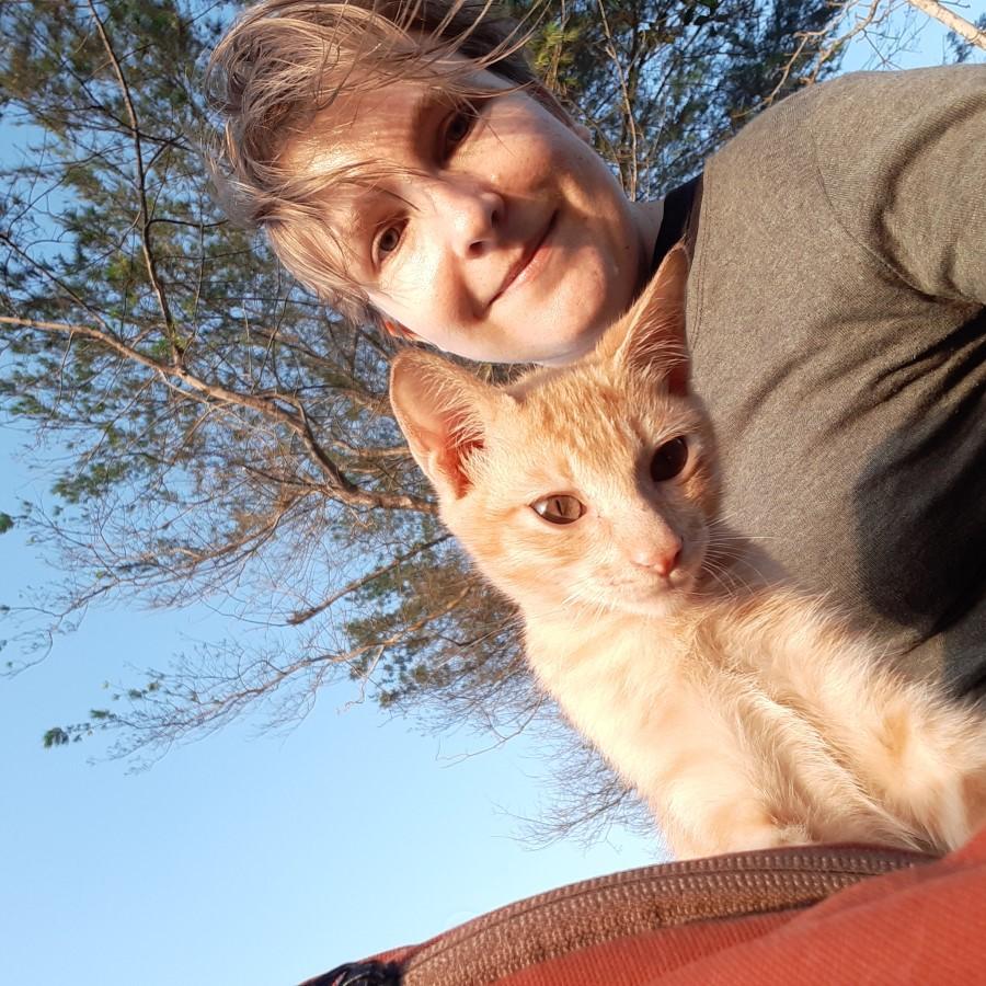 Auf dem Selfie lächelt Steffi in die Kamera. Neben Steffi sitzt ein orange getigertes Kitten auf einem braunroten Rucksack (der ist nur angeschnitten zu sehen) und schaut neugierig auf das Telefon, mit dem das Selfie gemacht wurde. Im Hintergrund sind blauer Himmel und Nadelbäume sichtbar.