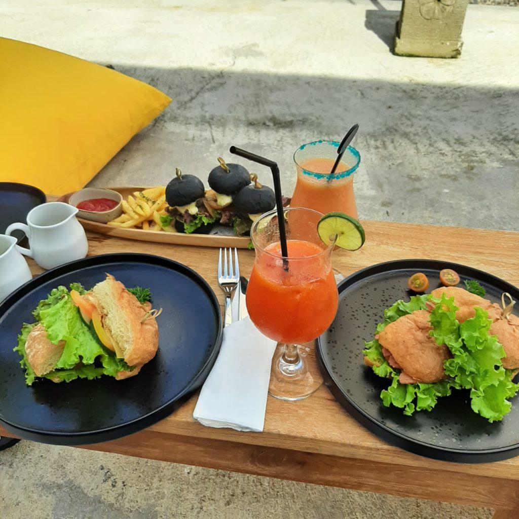 Auf einem niedrigen Holztisch stehen zwei schwarze Teller mit Sandwiches darauf, im Hintergrund steht ein länglicher schmaler Holzteller mit drei schwarzen Miniburgern und Pommes, dazwischen liegt Besteck und stehen Gläser mit Säften.